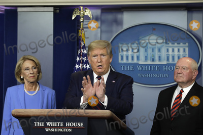 Devo Photo - United States President Donald J Trump speaks between US Secretary of Education Betsy DeVos left and US Secretary of Agriculture Sonny Perdue and Agriculture Secretary Sonny Perdue during a press briefing on the Coronavirus COVID-19 pandemic with members of the Coronavirus Task Force at the White House in Washington DC on March 27 2020  Credit Yuri Gripas  Pool via CNPAdMedia
