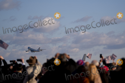 American Flag Photo - Supporters of US President Donald Trump hold American flags as Air Force One departs during a farewell ceremony at Joint Base Andrews Maryland US on Wednesday Jan 20 2021 Trump departs Washington with Americans more politically divided and more likely to be out of work than when he arrived while awaiting trial for his second impeachment - an ignominious end to one of the most turbulent presidencies in American history Credit Stefani Reynolds  Pool via CNPAdMedia