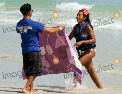 Run DMC Photo - American socialite and entrepreneur Angela Simmons best known as the daughter of Run-DMCs Rev Run and neice of hip-hop legend Russell Simmons wears a silver bikini paired with a floppy red scarf on her head as she spends an afternoon with a friend soaking up the sun on trendy South Beach Angela looked like she had a blast while jet skiing and donned a zebra-print cover-up as she strolled with her friend on the sand Miami Beach FL  3111