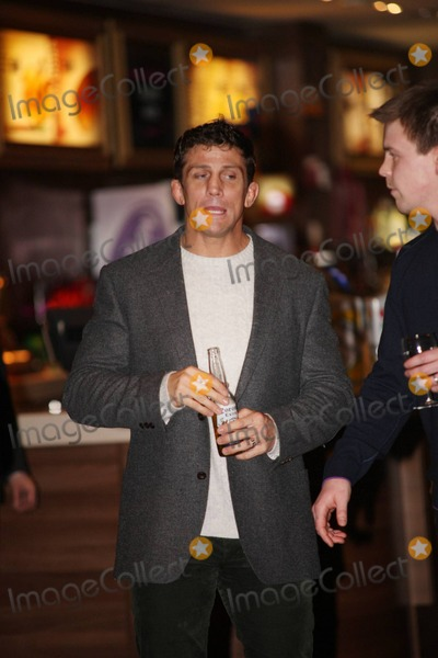 Alex Reid Photo - Mix-martial artist Alex Reid soon-to-be ex-husband of glamour model Katie Price (aka Jordan) appears in good spirits as he gives the thumbs up and drinks a beer at the premiere of Zebra Crossing held at Empire Leicester Square  Alex who wore his wedding ring looked relaxed while hanging out among the other guests including actress Emma Rigby despite reports that Katie has decided to sell up house and move to the country because he refuses to leave the home they once shared London UK 012611