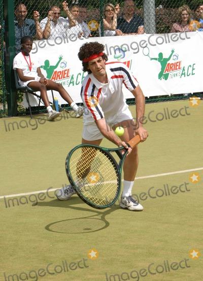 Alistair McGowan Photo - Wimbledon Alistair McGowan dressed as John McEnroe circa early eighties playing Tim Henman at Tim Henmans Ariel Tennis Ace search at Wimbledon14 June 2004PAULO PIREZLANDMARK MEDIA