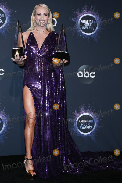 Carrie Underwood Photo - LOS ANGELES CALIFORNIA USA - NOVEMBER 24 Singer Carrie Underwood wearing a Stello dress Giuseppe Zanotti shoes a Jimmy Choo clutch and jewelry from Yvan Tufenkjian and Maxior poses in the press room at the 2019 American Music Awards held at Microsoft Theatre LA Live on November 24 2019 in Los Angeles California United States (Photo by Xavier CollinImage Press Agency)