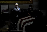 Photo - Light is cast on a US Capitol Police Honor Guard member as Rep Kim Young (R-Calif) pays her respects to US Capitol Police officer William Evans as he lies in honor at the Capitol in Washington DC on Tuesday April 13 2021Credit Greg Nash  Pool via CNPAdMedia